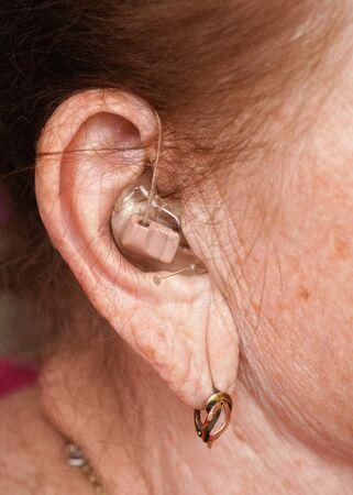 Hearing aid device in senior woman ear - closeup photo.