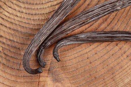 Vanilla beans on wooden board, closeup photo from above. Banco de Imagens