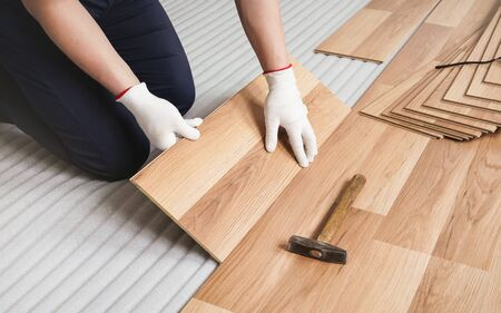 Man installing laminated floor, detail on wooden tile being fitted, over white foam base layer.