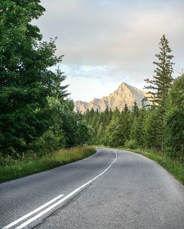Asphalt road in forest, coniferous trees on both sides, mount Krivan peak Slovak symbol with afternoon sun clouds, in distance.