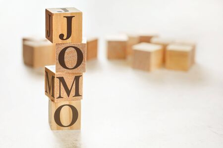 Four wooden cubes arranged in stack with text JOMO meaning Joy of missing out on them, space for text image at down right corner.