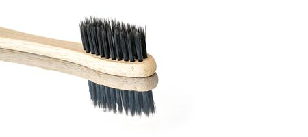 Wooden bamboo toothbrush with black bristles, closeup detail isolated on glossy white table reflection visible , space for text right side.