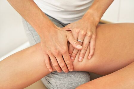 Female physiotherapist massaging exercising muscles at knee, closeup on her hands.