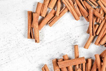 Cinnamon bark sticks on white stone like board, overhead photo.