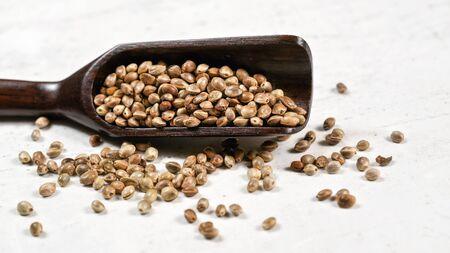 Unpeeled hemp - Cannabis sativa - in small dark wooden spoon on white stone board desk.