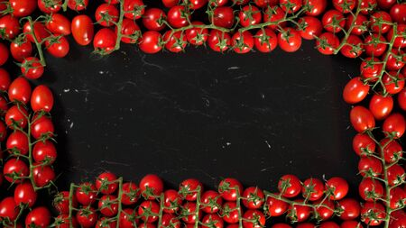 Group of red cherry tomatoes on black marble like board, view from above. They form frame with space for text in middle.