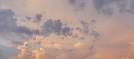 Orange and violet clouds on sunset sky background.