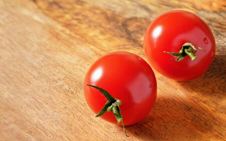Two bright red cherry tomatoes on wooden board, space for text left side. Detailed close up macro.