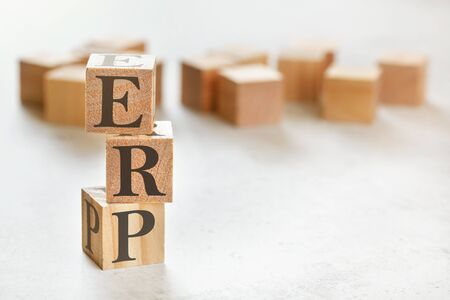 Three wooden cubes with letters ERP means Enterprise resource planning , on white table, more in background, space for text in right down corner.