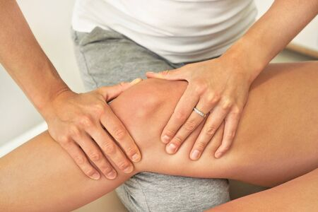 Female caucasian physiotherapist holding massaging knee of patient, closeup on her hands