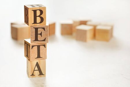 Four wooden cubes arranged in stack with word BETA on them, space for text image at down right corner. Stock Photo