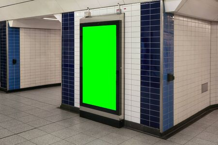 Advertising board display green mockup on wall with white tiles at underground station passage