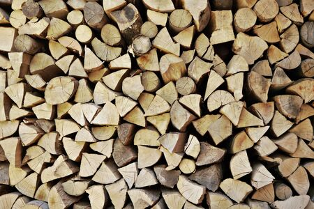 Wooden logs cut to pieces stacked as firewood near house. Stockfoto
