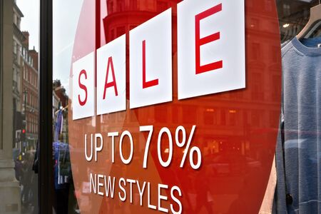 Sale up to seventy percent new styles sign - white letters in red circle - on glass window of clothes shop.