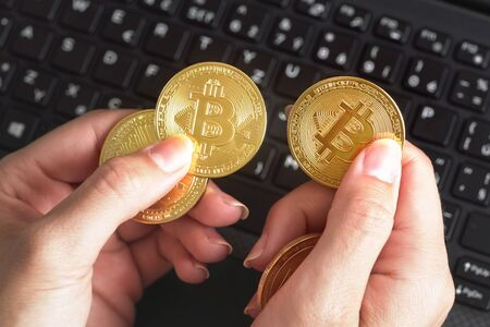 Woman hand holding golden coloured bitcoin coins over black laptop keyboard Zdjęcie Seryjne