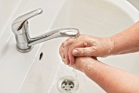 Senior woman washing her hands with soap under tap water faucet. Can be used as hygiene illustration concept during ncov coronavirus / covid 19 outbreak Standard-Bild