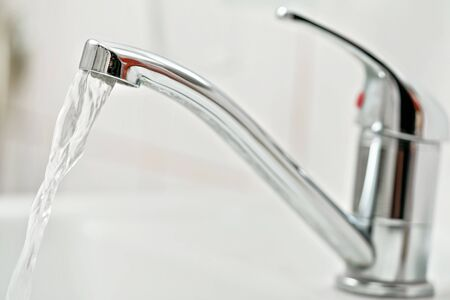 Chrome tap faucet with water flowing, blurred bathroom background