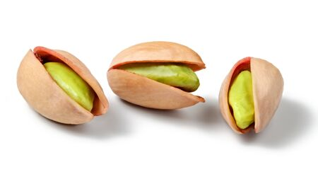 Three Turkish red pistachios (Antep), isolated on white background. Peeled green nuts visible inside.