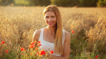 Young woman sitting in wheat field, lit by afternoon sun, few red poppies around her in foreground.