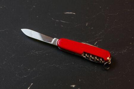 Red pocket knife on black table.