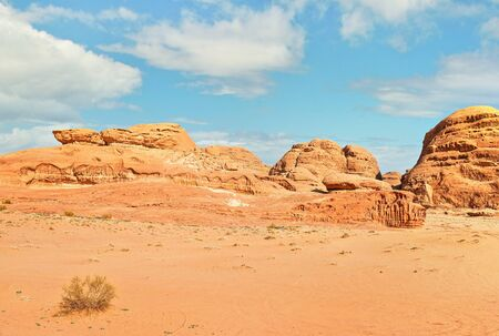 Rocky formations and mountains in sandy desert, blue sky above, typical scenery in Wadi Rum, Jordan