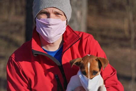 Jack Russell terrier wearing white cotton mouth mask, owner in red jacket with virus face mask in background. Pets are not vulnerable to coronavirus covid-19 but some owners protect them nevertheless