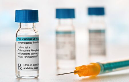 Chloroquine phosphate drug in small injection bottles with blue caps, orange green syringe near, closeup detail (own label design with dummy data - not real product) Potential coronavirus cure concept