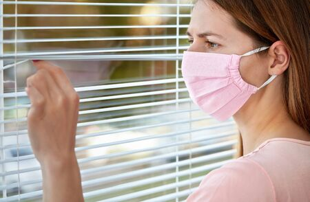 Young woman in pink home made cotton virus face mask, looking through window blinds outside. Quarantine or stay at home during coronavirus covid-19 outbreak