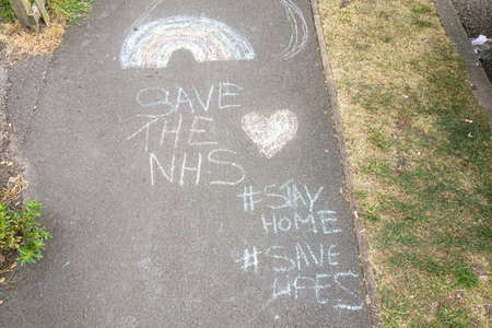 London, United Kingdom - April 27, 2020: Thank you note to NHS, rainbow, and advice to stay at home, drawn by kid on pedestrian pavement in Lewisham during coronavirus covid-19 outbreak