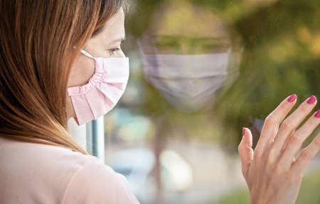 Young woman in pink virus mask looking sad from the window behind glass pane, touching it with hand. Quarantine or stay at home to be safe during coronavirus covid-19 outbreak concept 版權商用圖片