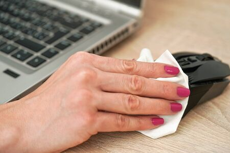 Woman cleaning black computer mouse, about to spray disinfect on it, holding back with paper tissue, closeup detail on hands with pink fingernails
