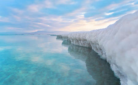 Sand completely covered with crystalline salt looks like ice or snow on shore of Dead Sea, turquoise blue water near, sky colored with morning sun distance - typical scenery at Ein Bokek beach, Israel Stock fotó