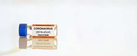 Coronavirus Covid-19 vaccine concept - small glass vial with blue cap on white table, closeup detail wide banner space for text right side (sticker is own design with dummy data, not a real product)
