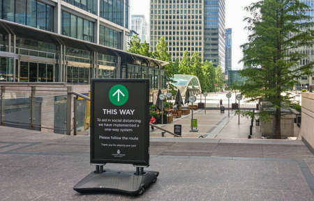 London, United Kingdom - June 14, 2020: Advisory note sign at Canary Wharf station, prompting pedestrians to walk only one way to help with social distancing during coronavirus covid - 19 outbreak