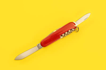 Tabletop view, red pocket knife, with both blades opened, laying on yellow board.