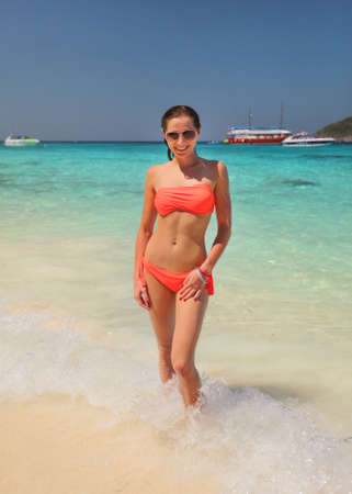 Young woman in orange bikini ad sunglasses standing in shallow water, turquoise sea behind her.