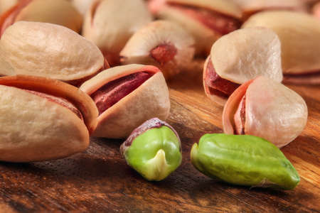 Pile of red Turkish pistachios on wooden board. Two of them peeled, green nut visible. Reklamní fotografie