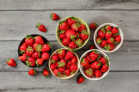 Tabletop view - five small bowls with strawberries, some of them spilled on gray wood desk. Reklamní fotografie