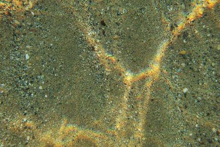 Underwater photo, shallow sea bottom floor seen from top, light refraction making rainbow glares on sand. Abstract marine background.
