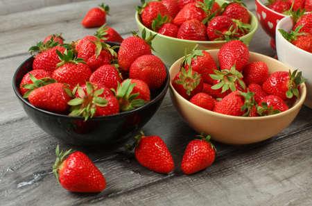 Bowls with strawberries on gray wooden desk. Reklamní fotografie