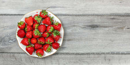 Tabletop view - plate with strawberries on gray wooden desk, place for text on right.