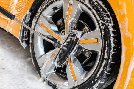 Yellow car wheel washed in self service carwash, brush cleaning aluminium rim disc covered in shampoo Reklamní fotografie