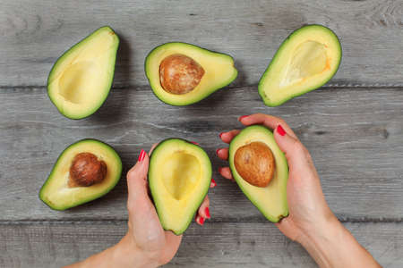 Tabletop view - woman hands with red nails, hold avocados cut in half, more halves with seed visible on gray wood desk.