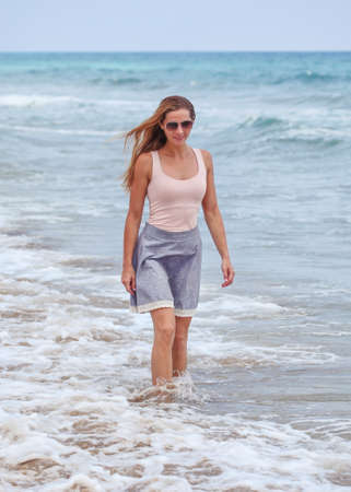 Sporty young woman in skirt, t shirts and sunglasses standing in shallow sea, small waves and overcast sky behind her.