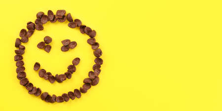 Tabletop view, smiley face made of brow chocolate corn flakes on yellow board. Space for text on right side.