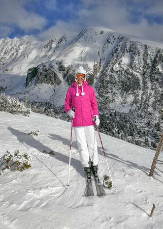 Young woman in pink jacket,  ski, boots, poles, gloves and hat, posing on the piste, snow covered mountain behind her during sunny day.