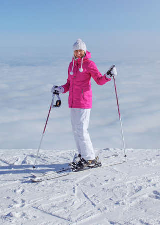 Woman in pink jacket, ski poles and skis, standing at the edge of hill, only clouds below, looking back, smiling