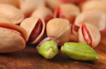 Closeup of Turkish red pistachios, roasted and salted, two of them peeled, green nut visible, on wooden board.