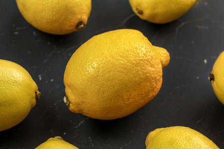 Top view - whole lemons on black marble board.