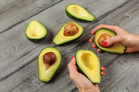 Avocado halves on gray desk, woman hands with red nails hold two of them.
